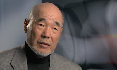 Older Asian man being interviewed